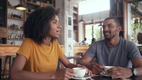 Giovane donna che mangia caffè con il suo amico in caffè stock footage