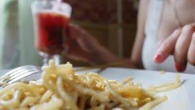 Giovane donna che mangia gli spaghetti in caffè stock footage