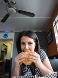 Giovane donna che mangia hamburger Fotografia Stock Libera da Diritti