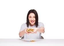 Giovane donna che mangia hamburger isolato su bianco Fotografia Stock