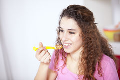Giovane donna che mangia i cereali Fotografia Stock