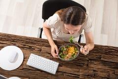 Giovane donna che mangia insalata immagini stock libere da diritti