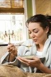 Giovane donna che mangia minestra fotografie stock