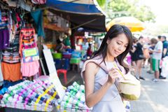 Giovane donna che mangia noce di cocco succosa nel mercato di strada Fotografia Stock Libera da Diritti