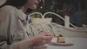 Giovane donna che mangia piccolo pezzo di fine saporita del dolce su nel caffè La ragazza che gode del suo dessert nel moderno video d archivio