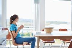 Giovane donna che mangia prima colazione nella cucina Fotografia Stock
