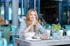 Giovane donna che mangia prima colazione sana in all'aperto Fotografia Stock