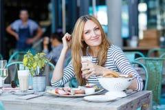 Giovane donna che mangia prima colazione sana in caffè all'aperto Immagine Stock