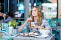 Giovane donna che mangia prima colazione sana in caffè all'aperto Fotografie Stock Libere da Diritti