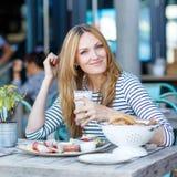 Giovane donna che mangia prima colazione sana in caffè all'aperto Fotografia Stock