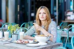 Giovane donna che mangia prima colazione sana in caffè all'aperto Fotografie Stock