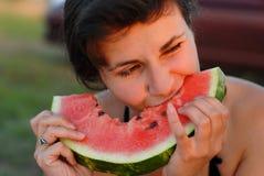 Giovane donna che mangia un'anguria fotografia stock