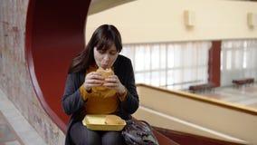 Giovane donna che mangia un hamburger all'interno archivi video
