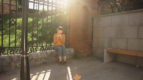 Giovane donna che mangia un hamburger sulla via vicino ad un recinto della ghisa al tramonto stock footage