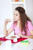 Giovane donna che mangia yogurt Fotografie Stock Libere da Diritti