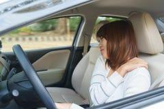 Giovane donna che massaggia il suo braccio o spalla mentre conducendo un'automobile af Fotografia Stock Libera da Diritti