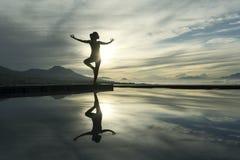 Giovane donna che medita al poolside immagine stock libera da diritti