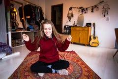 Giovane donna che medita al suo appartamento Fotografie Stock