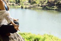 Giovane donna che medita dall'acqua Immagini Stock Libere da Diritti