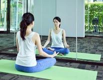 Giovane donna che medita davanti allo specchio nella stanza di yoga, raggiro di yoga Fotografia Stock