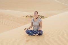 Giovane donna che medita nel deserto immagini stock libere da diritti