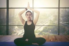 Giovane donna che medita nell'appartamento immagini stock libere da diritti