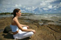 Giovane donna che meditating alla spiaggia Immagine Stock
