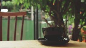 Giovane donna che mescola la tazza di caffè nel caffè Fotografie Stock