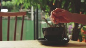 Giovane donna che mescola la tazza di caffè nel caffè Fotografia Stock Libera da Diritti
