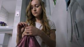 Giovane donna che mette lavanderia nella lavatrice video d archivio