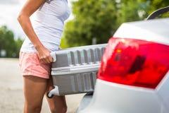Giovane donna che mette una valigia nel suo tronco dell'automobile Immagine Stock Libera da Diritti