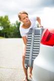 Giovane donna che mette una valigia nel suo tronco dell'automobile Fotografia Stock Libera da Diritti