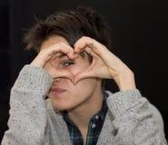 Giovane donna che modella cuore con le dita sul nero Fotografie Stock