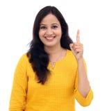 Giovane donna che mostra il dito indice contro il bianco fotografia stock libera da diritti