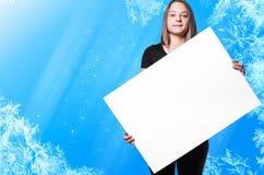 Giovane donna che mostra insegna in bianco fotografia stock