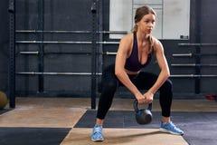 Giovane donna che occupa con i pesi nella palestra di CrossFit Fotografie Stock Libere da Diritti