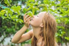 Giovane donna che odora il frutto della passione nel giardino immagini stock