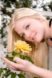 Giovane donna che odora Rosa gialla Fotografia Stock