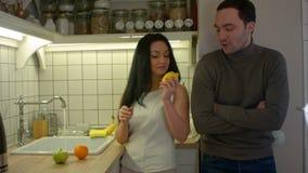 Giovane donna che offre al suo ragazzo frutta fresca nella loro cucina nella sera video d archivio