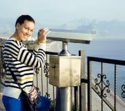 Giovane donna che osserva tramite il telescopio il punto di vista del mare in Atatur Fotografie Stock