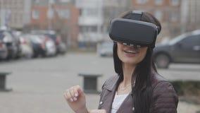 Giovane donna che ottiene esperienza di per mezzo della VR-cuffia avricolare o della cuffia avricolare di realtà virtuale all'ape video d archivio