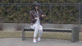 Giovane donna che ottiene esperienza di utilizzare VR-cuffia avricolare o la cuffia avricolare di realtà virtuale all'aperto ment video d archivio