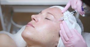 Giovane donna che ottiene iniezione cosmetica in fronte stock footage