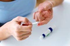 Giovane donna che ottiene la prova del glucosio con il glucometer a casa Concetto trattato sbagliato fotografia stock