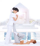 Giovane donna che ottiene massaggio d'allungamento tailandese tradizionale dal thera Immagini Stock Libere da Diritti