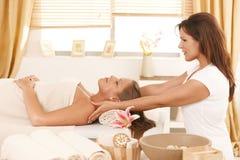 Giovane donna che ottiene massaggio nella stazione termale di giorno Fotografie Stock