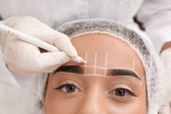 Giovane donna che ottiene pronta per la procedura di trucco permanente del sopracciglio nel salone del tatuaggio immagine stock libera da diritti