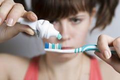 Giovane donna che ottiene pronta a pulire i denti Immagine Stock