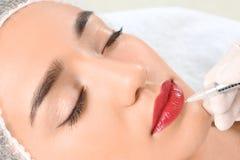 Giovane donna che ottiene trucco permanente sulle labbra immagini stock libere da diritti