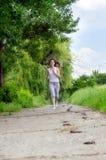 Giovane donna che pareggia attraverso una sosta Immagini Stock Libere da Diritti